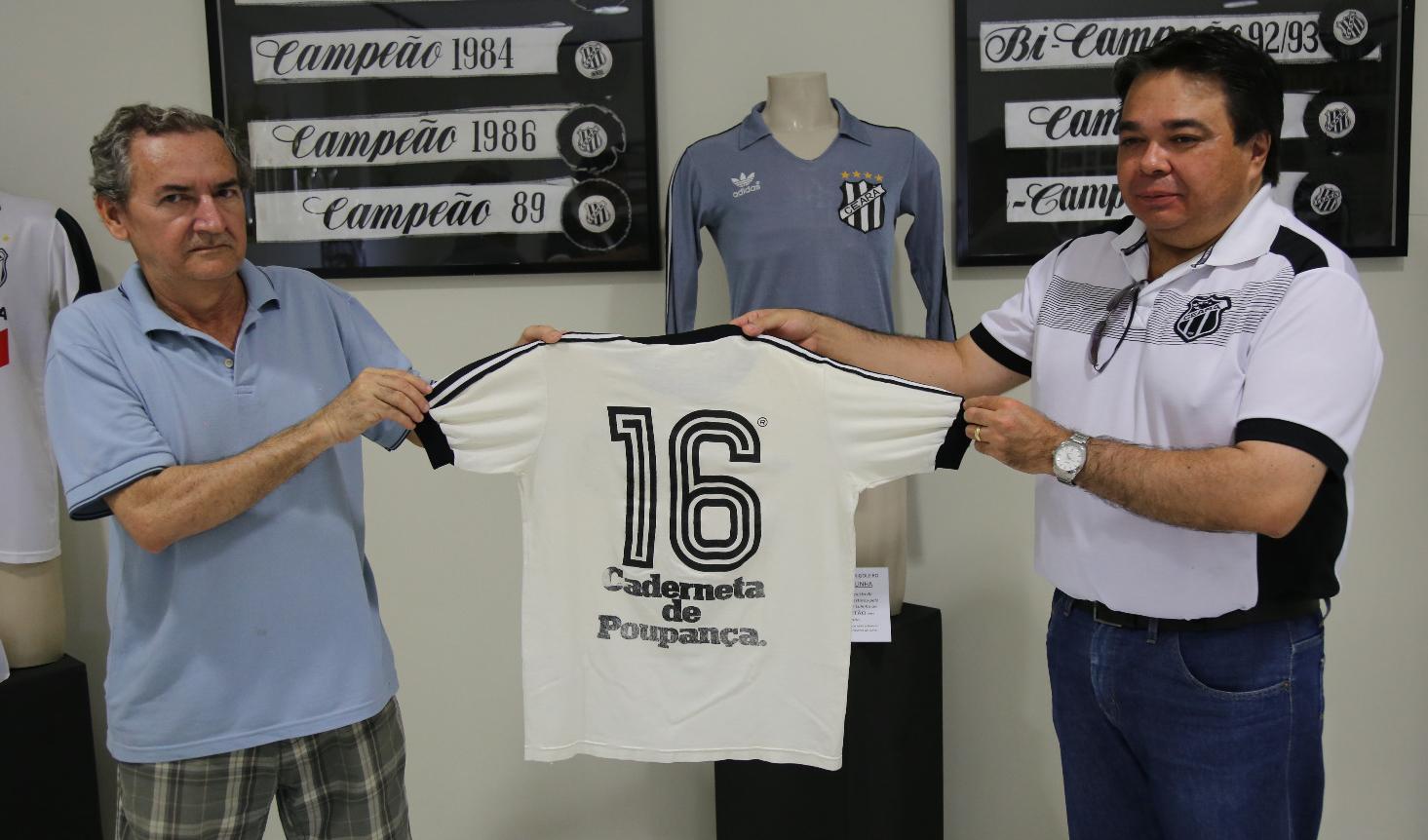 Pesquisador Eugênio Fernandes recebe a camisa das mãos de Vlamir Oliveira.